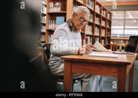 Senior man studying in classroom. Elderly man writing in a book sitting in classroom with a laptop in front. - Stock Photo
