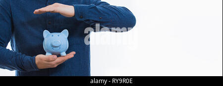 Close up of male body protecting piggy bank covering with both hands isolated over white background with copy space. Finance insurance, safe investmen - Stock Photo