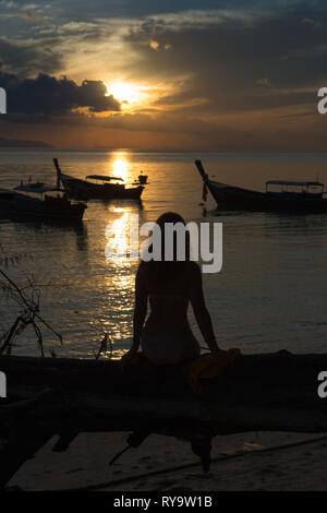 Silhouette of a girl sitting on a fallen tree on the beach, Ko Lipe, Thailand - Stock Photo