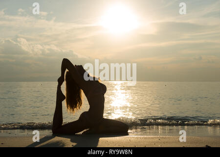 Silhouette of a girl in pigeon pose, practicing yoga on the beach, Thailand - Stock Photo