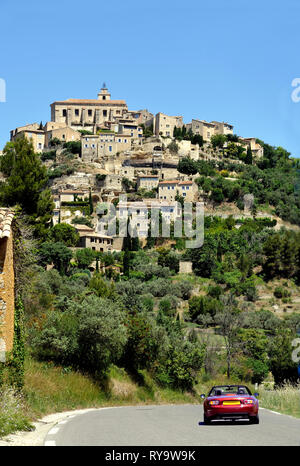 View at Menerbes in the Luberon, France with a sports car on the road leading to the village - Stock Photo