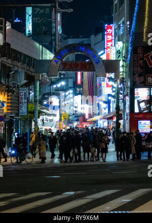 TOKYO, JAPAN - FEBRUARY 7, 2019: People in Ameyoko or Ameyayokocho market near Ueno station. A major shopping street in Tokyo. Japanese text advertise - Stock Photo