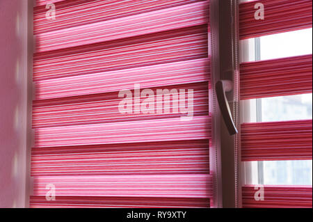 Fabric roller blinds on the window in the living room. - Stock Photo
