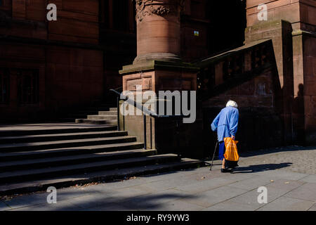 Old woman carrying shopping with stick seen from behind walking past Kelvingrove museum Glasgow Scotland uk - Stock Photo