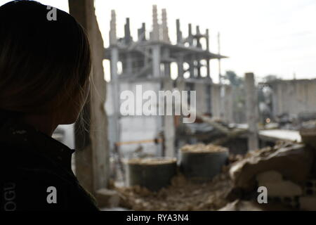 Destroyed buildings in Kobanî and YPJ fighter - Stock Photo