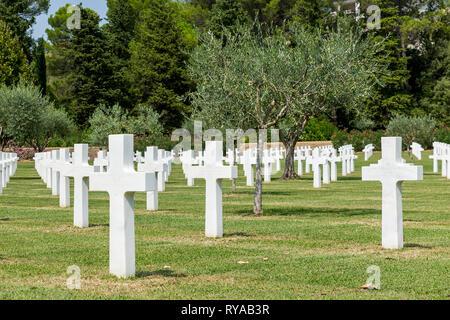 Grabkreuze auf dem Friedhof, zwischen den Grabkreuzen sind Olivenbaeume gepflanzt in Rhone American Cemetery and Memorial, Draguignan, Frankreich