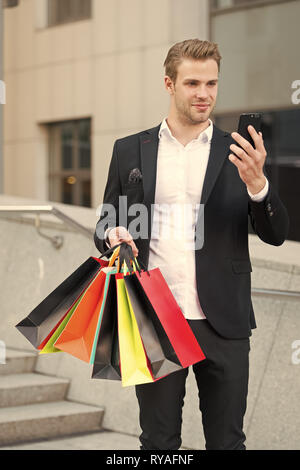 Man hold bags while check discount online with smartphone. Guy carry bunch shopping bags. Profitable deals shopping on black friday. Man hold paper ba