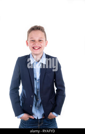 Boy in blue shirt and blue jacket laughs frontally into the camera - Stock Photo