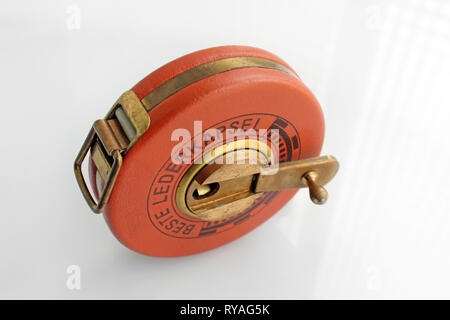 Old german roll measuring tape, isolated on white background, close-up - Stock Photo