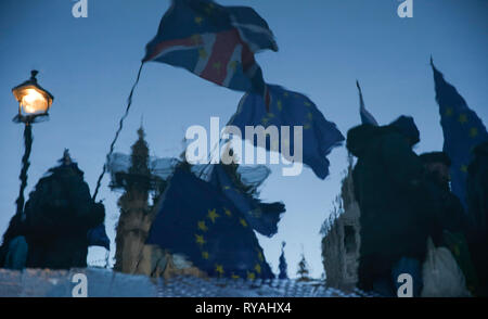 London, UK. 12th Mar, 2019. The reversed photo taken on March 12, 2019 shows demonstrators outside the Houses of Parliament in London, Britain. British Prime Minister Theresa May's Brexit deal was rejected again on Tuesday by MPs in the second meaningful vote in the parliament since January, increasing uncertainty about how the country will leave the European Union. Credit: Han Yan/Xinhua/Alamy Live News - Stock Photo