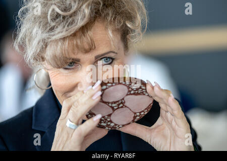 Erfurt, Germany. 13th Mar, 2019. Birgit Keller (Linke), Minister for Infrastructure and Agriculture, smells a blood sausage on the 23rd day of the Thuringian sausage specialities as part of the sausage test. The event takes place as part of the Thuringia exhibition (9.-17.3.) at Messe Erfurt. Credit: Michael Reichel/dpa/Alamy Live News - Stock Photo