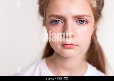 Sad and upset little girl having teardrop on her cheek - Stock Photo