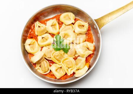 tortellini on white with tomato sauce - Stock Photo