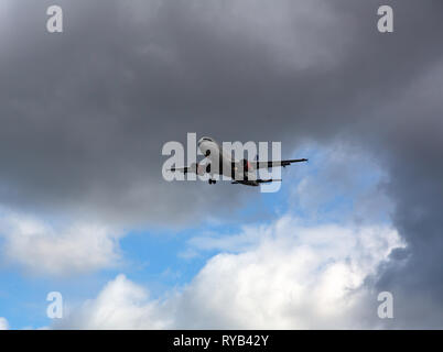 GERMANY, FRANKFURT - SEPTEMBER 06, 2015: Airbus A320-232, OY-KAP of SAS flies in the black stormy sky - Stock Photo