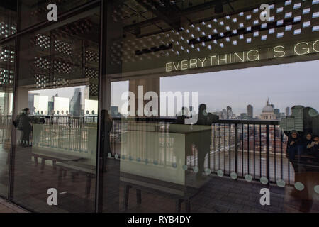 Reflection of people looking over balcony at the Tate Modern Gallery at London city view including St Paul's Cathedral.  London. - Stock Photo