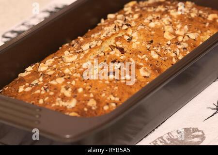 Freshly baked banana bread with hazelnuts topping - Stock Photo
