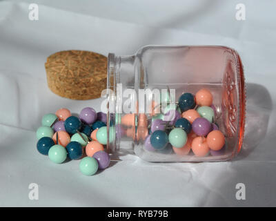 A glass jar of push pins photographed on a white background from a side angle, on its side with push pins split out and lid by the side - Stock Photo
