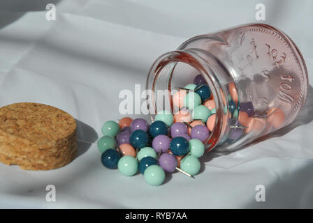 A glass jar of push pins on its side with push pins split out and the lid next to it - Stock Photo