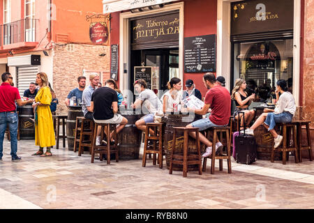 Tourists drinking and eating on a terrace at a Mitjana taverna from Malaga historic center, Spain - Stock Photo