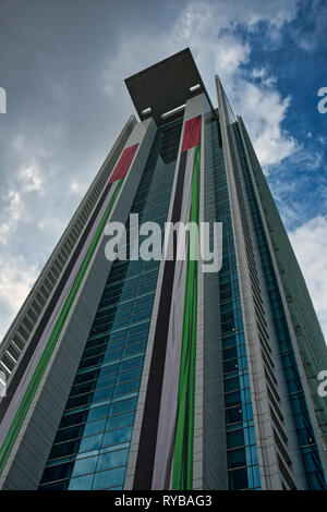 November 28, 2018 - Abu Dhabi, UAE: Exterior view of the ADCB building pasted with UAE flag - Stock Photo