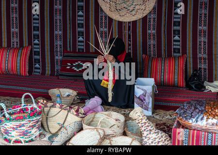 November 28, 2018 - Abu Dhabi, UAE: An Arabi tribal woman handcrafting baskets with date palm leaves. - Stock Photo