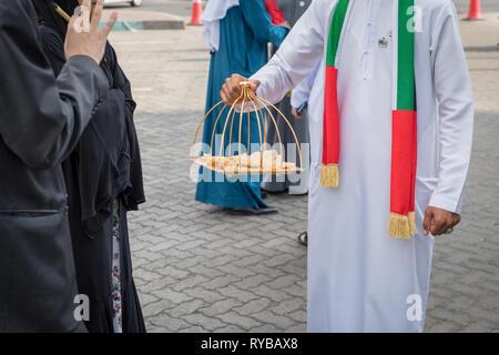 November 28, 2018 - Abu Dhabi, UAE: Local emirati women are being served with snacks on UAE Flag day - Stock Photo
