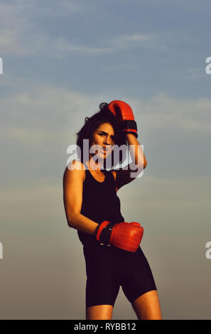boxing girl boxer against blue sky in red gloves - Stock Photo