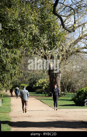 People walking along a gravel track path during the day in the sunshine in Oxford University Parks in winter / spring - Stock Photo