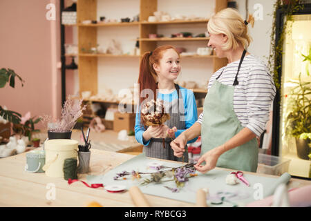 Waist up portrait of smiling mature woman creating flower compositions with teenage girl in art studio, copy space - Stock Photo