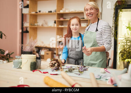 Waist up portrait of smiling mature woman looking at camera while creating flower compositions with teenage girl in art studio, copy space - Stock Photo