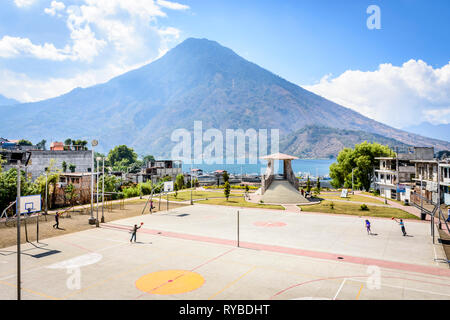 Santiago Atitlan, Lake Atitlan, Guatemala - March 8, 2019: Kids play in lakeside basketball court with San Pedro volcano behind in large lakeside town - Stock Photo