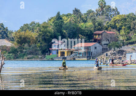 Santiago Atitlan, Lake Atitlan, Guatemala - March 8, 2019: Men paddle traditional canoes near lake shore in largest lakeside town - Stock Photo