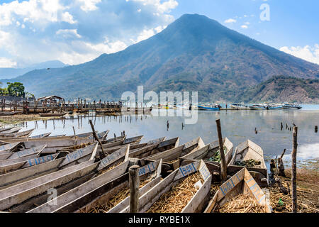 Santiago Atitlan, Lake Atitlan, Guatemala - March 8, 2019: Rows of lakeside traditional canoes with San Pedro volcano behind in largest lakeside town - Stock Photo