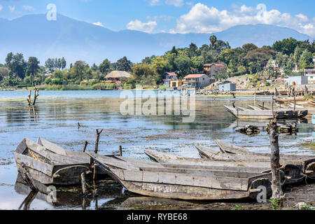 Santiago Atitlan, Lake Atitlan, Guatemala - March 8, 2019: Rows of lakeside traditional canoes by lake in largest lakeside town - Stock Photo