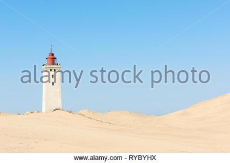 Old abandoned lighthouse on the sand dune near the coastline. Rubjerg Knude, Denmark - Stock Photo