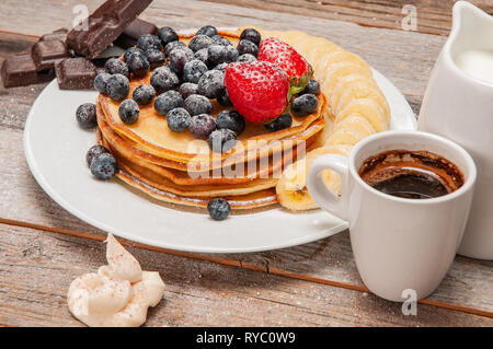 Healthy breakfast, coffee and delicious pancakes with fresh berries and banana, on wooden table. - Stock Photo