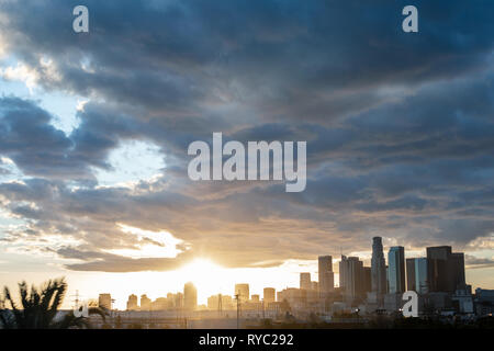 Gorgeous panoramic view of DTLA downtown Los Angeles with the sun setting behind skyscrapers - Stock Photo