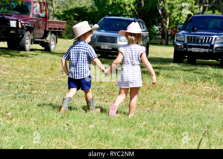 CHILDREN WALKING HAND IN HAND - Stock Photo