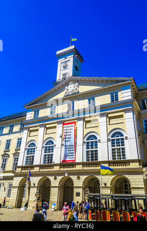Lviv Town Hall Side Low Angle View with Waving Ukrainian Flag on Roof - Stock Photo