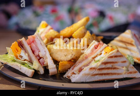 Club sandwich, take away food. Toasted bread slices, cheese, ham, egg, lettuce, french fries, closeup view - Stock Photo