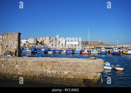 View of traditional Spanish fishing trawlers in the harbour with Tarifa castle to the rear, Tarifa, Cadiz Province, Spain. - Stock Photo
