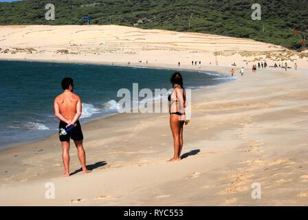 TARIFA, SPAIN - SEPTEMBER 14, 2008 - Couple standing at the waters edge on Valdevaqueros beach with kite surfers to the rear, Tarifa, Cadiz Province,  - Stock Photo