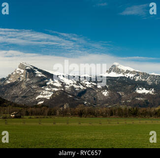 panorama mountain landscape in the Rhine Valley of Switzerland near Sargans with a green meadow in the foreground in late winter - Stock Photo