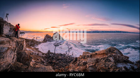 Landscape of Shamanka rock at sunset with natural breaking ice in frozen water on Lake Baikal, Siberia, Russia. - Stock Photo