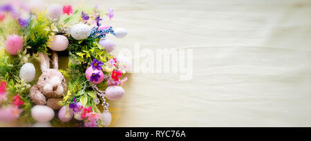 a colorful easter bunny wreath with colored eggs and flowers and pastel green  copy space background - Stock Photo