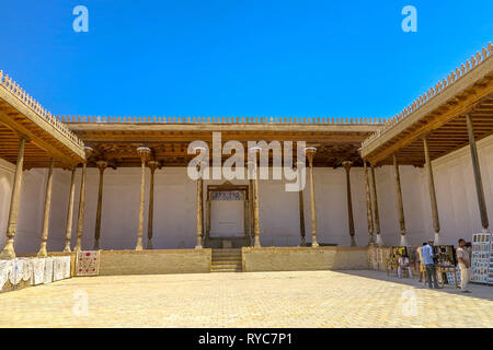 Bukhara Old City Ark Citadel Courtyard with Wooden Columns and Souvenir Sellers - Stock Photo
