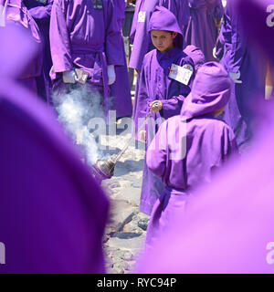 Young boy with incense during the procession of the cucuruchos in Antigua during Easter on Holy Friday, Guatemala. - Stock Photo