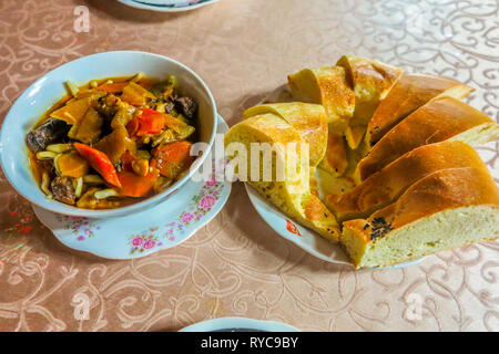 Uzbek Traditional Lagman Noodles Dish with Vegetables and Naan Bread - Stock Photo