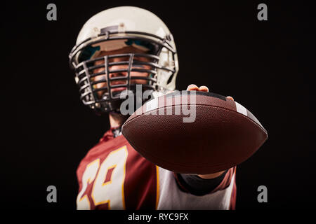 portrait of american football player standing with ball in foreground - Stock Photo