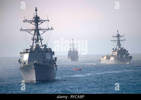 The U.S Navy Arleigh Burke-class guided-missile destroyers USS Nitze, left, the USS Bainbridge, and the Ticonderoga-class guided-missile cruiser USS Leyte Gulf, center, underway in formation during an integrated live-fire exercise February 22, 2019 in the Atlantic Ocean. - Stock Photo